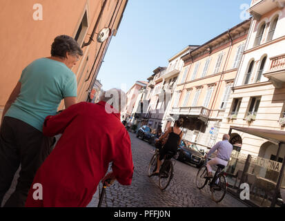 People walking and cycling along the quiet streets including elderly lady in a red coat, Sunday morning, Piacenza, Italy - Stock Image