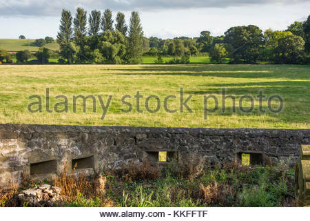 World War II defence loopholes in the graveyard wall at St Caduck's Church,  at The Bryn, Llanvihangel Gobion, - Stock Image