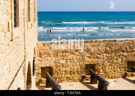Courtyard of Larnaca Fort looking over the walls to the sea beyond with bathers in the surf.Cyprus October 2018 - Stock Image