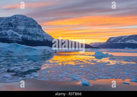 Greenland, Scoresby Sund, Gasefjord. Sunset with icebergs and brash ice. - Stock Image