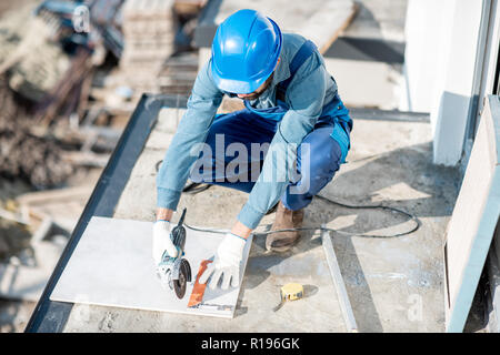 Workman in uniform mounting ceramic tiles on the balcony at the construction site - Stock Image