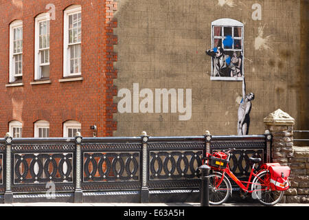 Banksy graffiti of man hanging from window. Humorous juxtaposition of postman's Royal Mail bike parked by railing. - Stock Image