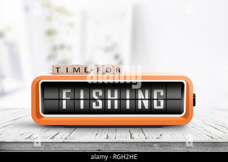 Retro alarm clock with the word fishing on a wooden table in a bright room - Stock Image