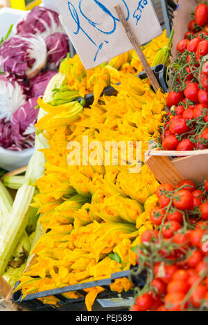 Italy Sicily Syracuse Siracusa Ortygia historic street fresh food & fish market bright yellow courgette flowers vegetable stall tomatoes radicchio - Stock Image