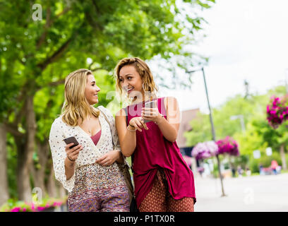 Two young women walk down a path on a university campus laughing and talking together as they look at their smart phones; Edmonton, Alberta, Canada - Stock Image