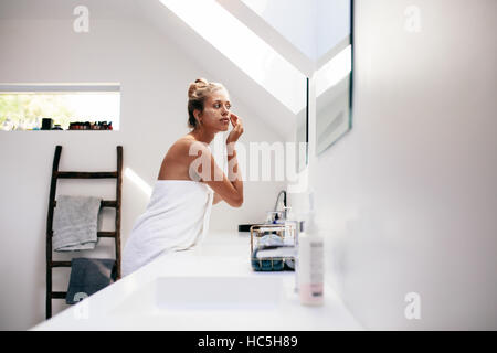 Young woman wrapped in towel looking in the mirror and applying cream on her face. Female taking care of her face - Stock Image