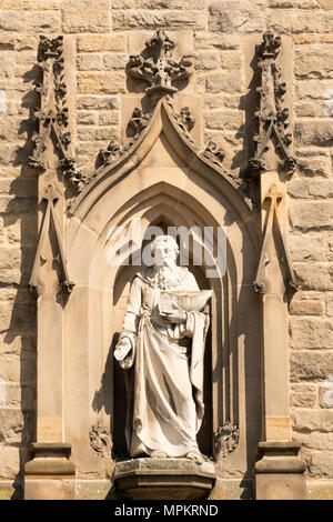 A statue of St Nicholas, holding a boat, above the  entrance to the  church of St Nicholas, Durham market place, England, UK - Stock Image