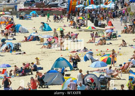 Lyme Regis, Dorset, UK.  4th July 2019. UK Weather.  Sunbathers on the beach at the seaside resort of Lyme Regis in Dorset enjoying a day of clear skies and scorching hot sunshine.   Picture Credit: Graham Hunt/Alamy Live News - Stock Image