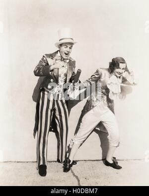Two people in 18th century costumes playing with firecrackers - Stock Image