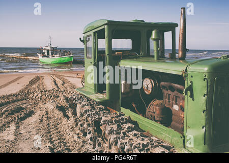 Tractor on the beach helps fishermen - Stock Image