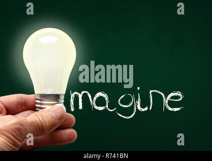 Man holding illuminated bulb with bare hands against chalkboard with the word Imagine. Concept of bright idea, innovation, imagination, inspiration, v - Stock Image
