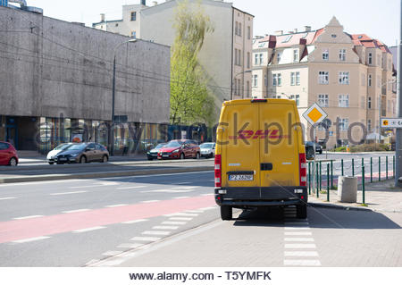 Poznan, Poland - April 18, 2019: Yellow DHL delivery bus parked along a road in the city center. The company is one of the most popular in the logisti - Stock Image