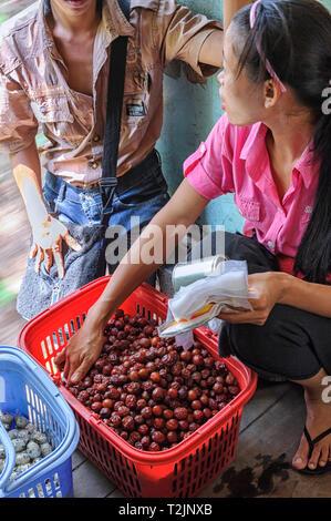 Woman selling snacks on the Circular train in Yangon Myanmar (Burma) - Stock Image