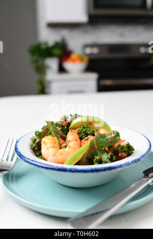 Food kale salad with shrimp and apple on it in a home kitchen - Stock Image