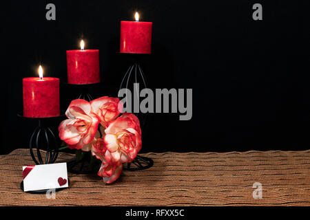 Beautiful orange and orange and white roses, red candle perched on black candle holders on mesh place mat and wooden table with dark background and ca - Stock Image