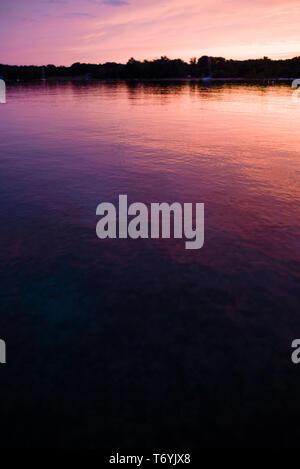 Dramatic sunset reflecting on surface of Lake Michigan - Stock Image