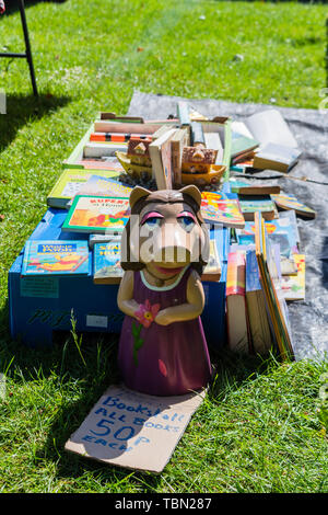 A ceramic Miss Piggy figure in front of a selection of second hand childrens books on a piece of plastic at a carboot sale - Stock Image
