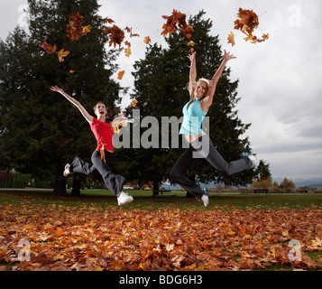 Two young cheerleaders do cheers with handfuls of autumn leaves, Spanish Bank, Vancouver, British Columbia, Canada - Stock Image