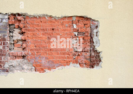 Stucco exterior wall with exposed or damaged area revealing weathered old brick pattern, suitable for a background with copy space or copyspace. - Stock Image