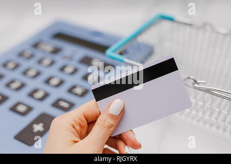 woman's hand holding payment card in front of huge calculator and shopping basket, concept of shopping budget - Stock Image