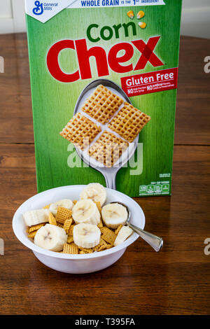 A bowl of Corn Chex with Bananas and a box of cereral - Stock Image