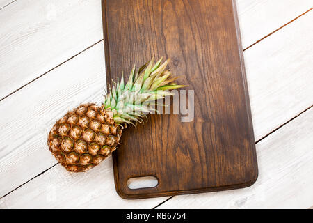 Fresh ripe pineapple on a white wooden background, top view. From above. Center - Stock Image
