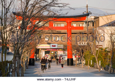 People riding bicycles under a traditional Japanese Torii gate at the entrance to the Fushimi Inari Taisha shrine, Fukakusa Yabunouchichō, Fushimi Wa - Stock Image