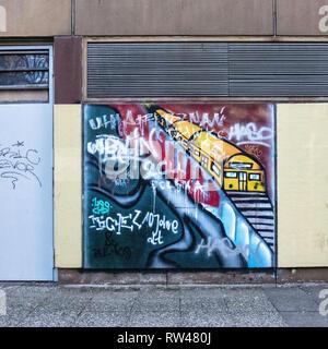 Berlin-Kreuzberg building with street art & graffiti. Picture of yellow train on raised viaduct - Stock Image