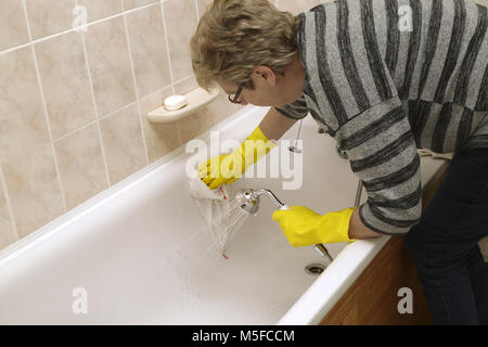 A woman cleaning a bath - Stock Image