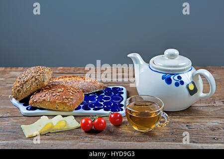 Studio shot of rolls and tea on a breakfast table - Stock Image