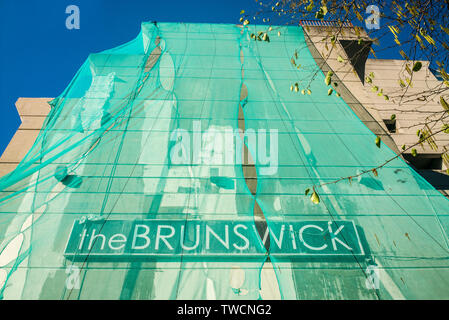 The Brunswick centre facade, green builders mesh, during building work - Stock Image