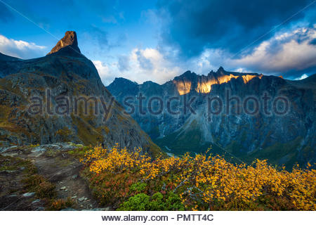 Autumn morning in Romsdalen valley, Møre og Romsdal, Norway.  The peak to the left is Romsdalshorn, 1550 m. The sunlit mountains in the background are the 3000 feet vertical Troll Wall and the peaks Trolltindane. Credit: Oyvind Martinsen/ Alamy Live News - Stock Image