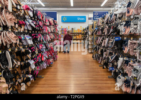 Two female customers in Walmart shoe department trying on shoes. Wichita, Kansas, USA. - Stock Image