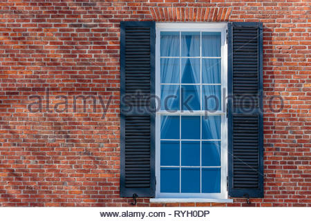 Window with shutters in brick wall of the Georgian Palladian architecture Campbell House Museum in Toronto Ontario Canada. - Stock Image