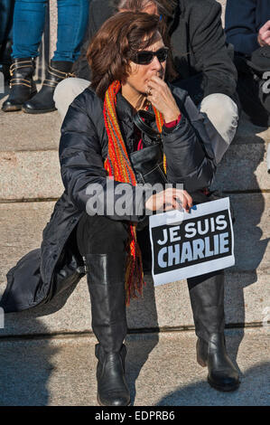 Geneva, Switzerland. 8th January 2015. A sad or pensive woman holding a sign of support during a vigil in Geneva's - Stock Image