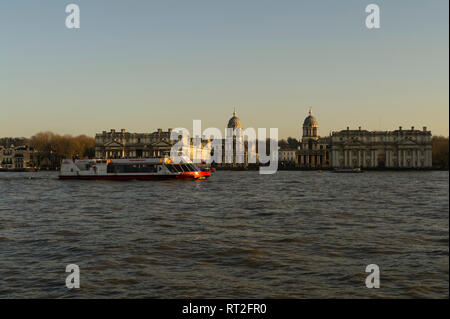 A London River Thames passenger Ferry passes the Old Royal Navy College in Greenwich. London, England, Great Britain. - Stock Image