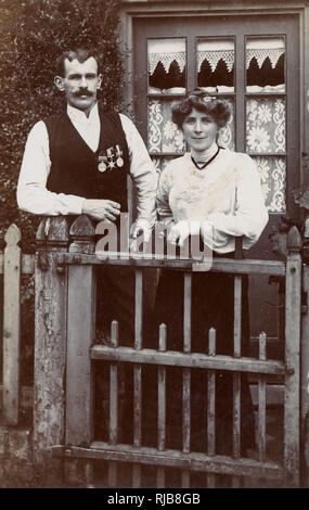Couple at gate, man wearing Boer War medals, showing that he was present at the Defence of Kimberley. - Stock Image