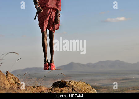 Maasai Warrior jumping with Crocs and beautiful scenic in background. Kenya, Africa. - Stock Image
