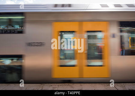A slightly blurred side on view of a Sydney Train departing from a railway station during the day - Stock Image