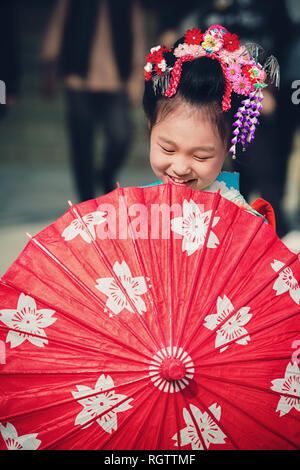 TOKYO, JAPAN - NOVEMBER 28, 2018: Japanese girl with umbrella posing during Shichi-Go-San day at Meiji shrine. Shichi-Go-Sun is annual festival day in - Stock Image