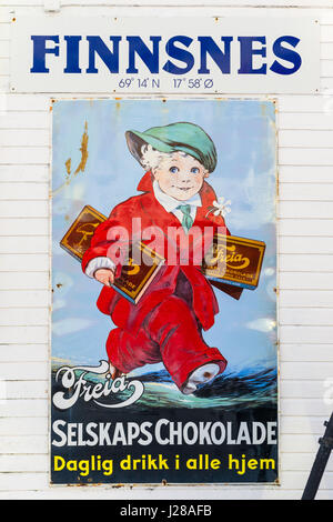 Vintage signboard advertising  chocolate at the port of Finnsnes, Troms County, Norway. - Stock Image