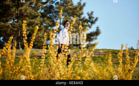 Businessman taking a walk at park during daytime - Stock Image