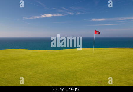 Red golf flag on Green with blue sea and sky behind. - Stock Image