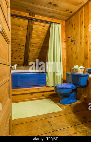 Blue toilet and bathtub in upstairs main bathroom inside an old circa 1760 Canadiana fieldstone cottage style house - Stock Image