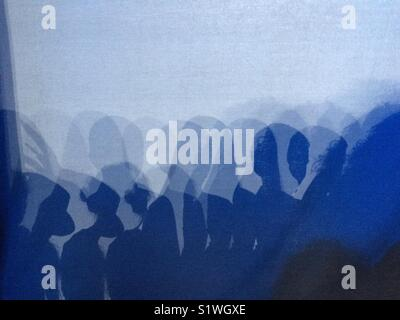Shadows of performers on back cyc on  stage. - Stock Image