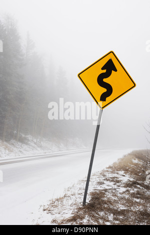 Curve sign in fog and snow on a mountain road. - Stock Image