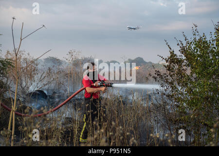 London, United Kingdom. 14 July 2018. Fifteen fire engines and 97 firefighters and officers were called to a grass fire on Staines Road in Feltham. Grass land the size of four football pitches is alight. Smoke from the fire has travelled near to Heathrow airport but it is not affecting their operations. Fourteen horses were removed from a nearby field to a place of safety. Credit: Peter Manning/Alamy Live News - Stock Image