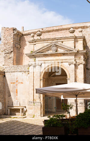Italy Sicily medieval walled town Erice on Monte San Giuliana cult Venus Erycina Piazza S Domenico St Square crucifix stone bench parasol cafe - Stock Image