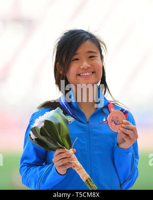 Doha, Qatar. 23rd Apr, 2019. Yue Ya Xin of Chinese Hong Kong reacts during the victory ceremony of the women's long jump final during 23rd Asian Athletics Championships at Khalifa International Stadium in in Doha, capital of Qatar, April 23, 2019. (Xinhua/Wu Huiwo) Credit: Wu Huiwo/Xinhua/Alamy Live News - Stock Image