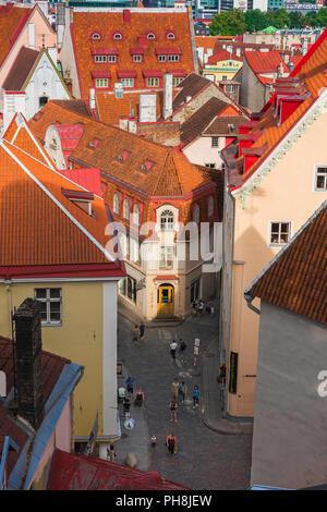 Tallinn street, view over orange tiled roofs towards a narrow street in the medieval Old Town quarter of Tallinn, Estonia. - Stock Image